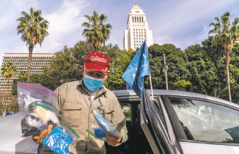 ?? Damian Do­var­ganes / As­so­ci­ated Press ?? Uber driver Jose Luis Gue­vara, a mem­ber of the Mo­bile Work­ers Al­liance, shows safety equip­ment he pro­vides to rideshar­ing cus­tomers out­side Los Angeles City Hall.