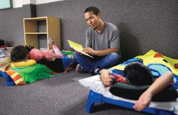 ?? JOHN LOCHER/ASSOCIATED PRESS ?? Darian Tharp reads during bedtime at the McCarran International Child Development Center, a 24-hour day care in Las Vegas, Nev., on Thursday night. Finding child care is difficult for those who work nontraditional hours.