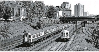 ?? BRIAN MORRISON. ?? With Class 423 4-VEP 7753 leading and Class 405/2 4-SUB 4356 also at the helm, the 1050 WaterlooGuildford and the 1046 Waterloo-Wimbledon-Richmond services respectively pass through Clapham Cutting on May 28 1982. Third rail was chosen for the Southern...