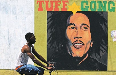 ?? Picture: AFP ?? RASTAMAN VIBRATION. A man pedals past a mural of Bob Marley in Kingston, Jamaica. It's been four decades since the death of the reggae superstar.