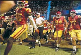 ?? Luis Sinco Los Angeles Times ?? CLAY HELTON, running onto the Coliseum field last Saturday, was admired for restoring integrity to the program but he could not meet its high standards.