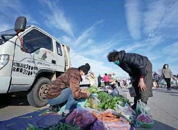 ??  ?? 市民在菜市场选购蔬菜