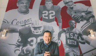 ?? RAJAH BOSE FOR THE WASHINGTON POST ?? Athletic Director Pat Chun poses in front of a mural depicting top Washington State athletes.