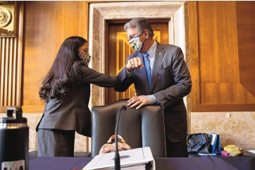?? GRAEME JENNINGS/VIA ASSOCIATED PRESS ?? Sen. Joe Manchin, D-W.Va., greets Rep. Deb Haaland, D-N.M., on Tuesday at the Capitol before the start of the Senate Committee on Energy and Natural Resources hearing on her nomination to be Interior secretary.
