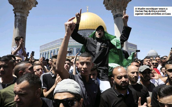 ?? Against Israeli airstrikes on Gaza ?? A Muslim worshipper wears a Hamas flag during a protest