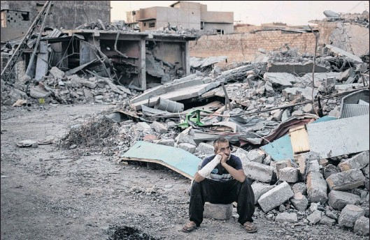 ?? FELIPE DANA/THE ASSOCIATED PRESS ?? Saddam Salih Ahmed, who was injured when his house was hit by an explosion, sits on his damaged street on the west side of Mosul, Iraq, July 13. Iraq's U.s.-backed forces succeeded in wresting Mosul from the Islamic State group but at the cost of...