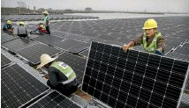 ??  ?? Solar power prices are dropping fast. Here Chinese workers install a floating field of panels in a heartland coal area.