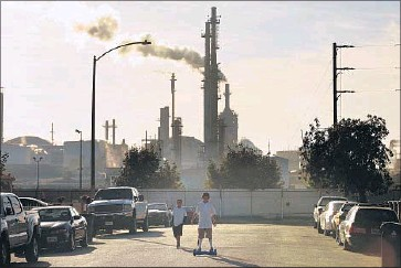 ?? Rick Loomis Los Angeles Times ?? CHILDREN play near the Phillips 66 refinery in Wilmington. No matter how hard California pushes, the country will fall short of its obligations under the Paris agreement unless more states try to keep pace.