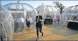 ?? AFP ?? An employee serves guests in domes at a restaurant in Chester, England.