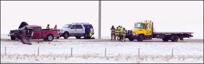 ?? Taber Times photo ?? Crews work at the scene of a collision Friday morning along Highway 36 between Taber and Vauxhall which resulted in the deaths of four people.