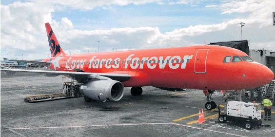 ?? Photo / Grant Bradley ?? The slogan on a Jetstar plane at Auckland Airport makes the airline's strategy very clear.