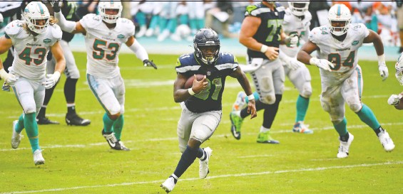 ?? JASEN VINLOVE/ USA TODAY ?? Seahawks running back DeeJay Dallas finds some room to make a big gain against the Dolphins during the second half of Seattle's 31-23 win in Miami on Sunday.