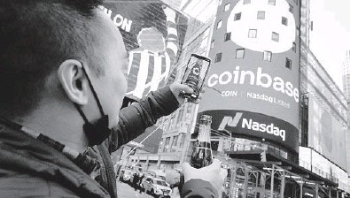?? RICHARD DREW/AP ?? Coinbase employee Daniel Huynh holds a bottle of Champagne as he takes a picture Wednesday outside the Nasdaq MarketSite in New York's Times Square. The digital currency exchange became a publicly traded company earlier this week.