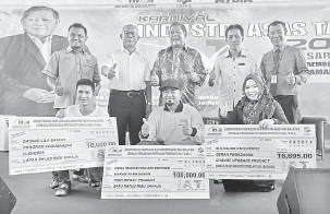 ??  ?? BANTU: Nogeh (tengah) ditemani Paza (dua kanan) dan Shukarmin (dua kiri) merakam kenangan bersama usahawan tempatan pada majlis tersebut.