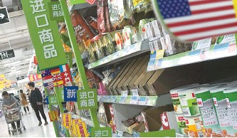 ?? AP-Yonhap ?? Women push a shopping cart near nuts and sweets imported from the United States and other countries displayed on a section selling imported foods at a supermarket in Beijing, Monday. China raised import duties on a $3 billion list of U.S. pork, fruit...