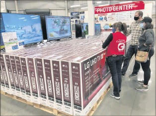 ?? THE ASSOCIATED PRESS ?? A sales associate helped customers as they considered the purchase of a big- screen television at a Costcowarehouse last week in Sheridan, Colo.
