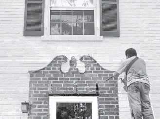?? JOHN KELLY/THE WASHINGTON POST ?? Carpenter Jesus Mateo chisels away some old adhesive that helped hold the pediment and pilasters that had been in place for 80 years at John Kelly's house in Silver Spring.
