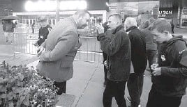 ?? RICK BOWMER/AP ?? A security guard looks for proof of vaccination or a negative COVID-19 test from fans looking to attend a preseason NBA game on Monday in Salt Lake City.
