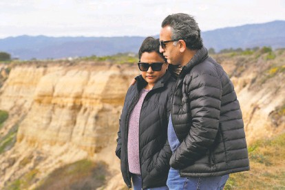 ?? Carlos Avila Gonzalez / The Chronicle ?? Top: Sharmistha (left) and Tarun Pruthi stop on the cliffs above Cowell Ranch State Beach where their son was washed away.