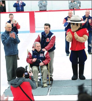 ??  ?? ABOVE: Mount St. Charles hockey Dave Belisle and his father, longtime Mount coach Bill Belisle, seated, receive the applause on the ice and in the stands at Adelard Arena in Woonsocket Friday night as they were honored for their long service to the school's hockey program before the season's final regular season R.I. Interscholastic League home game against Bishop Hendricken.