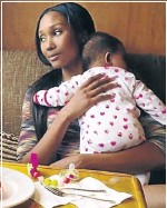 ??  ?? CUDDLE TIME: Mthiyane in deep thought as she holds her bundle of joy