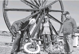 ?? SHARON MONTGOMERY-DUPE/CAPE BRETON POST ?? Former Cape Breton Regional Municipality councillor George MacDonald, left, lays a wreath at the Miners' Memorial Park in Glace Bay on June 11, 2020, accompanied by Mary Pat Mombourquette, executive director of the Cape Breton Miners' Museum, and Dan Jimmy White of Glace Bay, a 28-year former miner, to commemorate William Davis Day. Not unlike veterans of the Second World War, the 2,497 entries on the Nova Scotia Museum of History's list of coal mining fatalities in this province also fought battles against seemingly insurmountable odds, and made the ultimate sacrifice for their families and their communities.