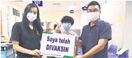 ??  ?? GIRANG: (Dari kiri) Chua, Moh dan Hii merakam gambar kenangan selepas masing-masing menerima suntikan vaksin COVID-19, semalam.