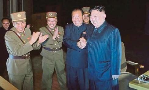 ??  ?? JONG-un (kanan) bersama pegawainya meraikan kejayaan ujian kedua peluru berpandu Hwasong-14 kelmarin. - EPA