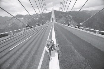 "?? DARIO LOPEZ-MILLS / ASSOCIATED PRESS ?? A worker crosses the median on the new cable-stayed bridge called the Baluarte in the western Sierra Madre near Concordia, Mexico. Sinaloa state tourism officials predict a tourist ""explosion"" for the resort city of Mazatlan."