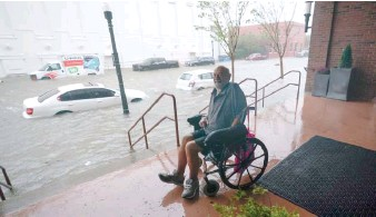 ?? GERALD HERBERT/AP ?? A man watches floodwaters in downtown Pensacola, Florida, on Wednesday.