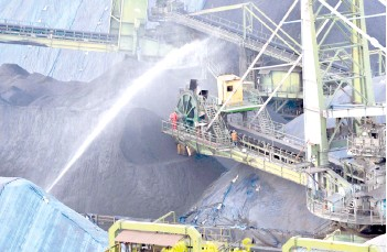 ??  ?? Water is sprayed onto a shipment of coal after being unloaded from a cargo vessel at the Mormugao Port Trust in Goa.