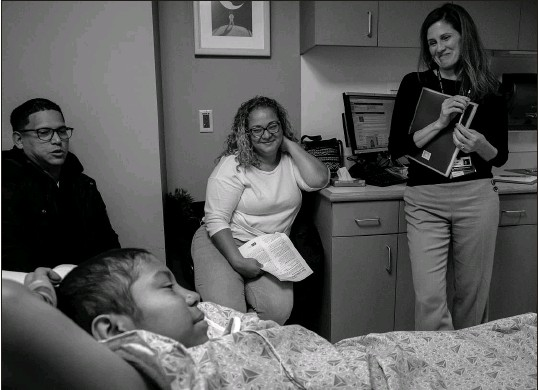 ?? PHOTOS BY HILARY SWIFT / THE NEW YORK TIMES ?? Above: Helen Obando is joined by her parents, Bryon Obando, left, and Sheila Cintron, center, and Dr. Erica Esrick on Dec. 16, 2020, at the Dana-farber Boston Children's Cancer and Blood Disorders Center in Boston. Below: Helen sits with her parents the previous day.