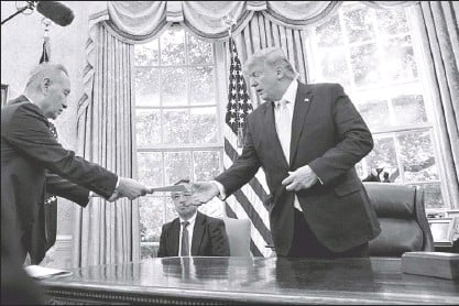 ?? AP ?? US President Donald Trump receives letter presented by Chinese Vice Premier Liu He (left) in the Oval Office of the White House in Washington Friday.