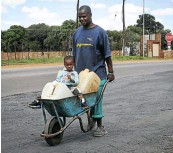 ??  ?? A man and his child return home after collecting water in Koster in North West.