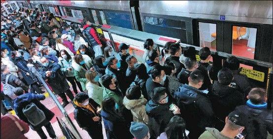?? ZHU ZHENQIANG / FOR CHINA DAILY ?? Commuters line up to board a subway train during the morning rush hour at Sihuidong station in Beijing in November.