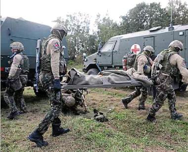 ??  ?? Die Soldaten simulieren bei der Übung, wie sie einen verwundeten Kameraden erstversorgen und anschließend in ein Rettungsfahrzeug transportieren.