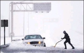 ?? Julio Cortez Associated Press ?? A DRIVER TRIES to dig out a vehicle on the New Jersey Turnpike. Icy and snow-covered roadways stranded motorists from Kentucky to Pennsylvania.