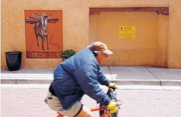 ?? LUIS SÁNCHEZ SATURNO/THE NEW MEXICAN ?? A bicyclist rides through Burro Alley on Wednesday, past the site where the city's Historic Districts Review Board struck down a proposed mural because it would be on vinyl attached to aluminum rather than painted on the wall of the building.