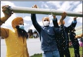 ?? JASON DECROW — AP PHOTO ?? Jasbir Singh, left, and Vijay Singh wash a flagpole with milk as part of a ceremonial changing of the Sikh flag during Vaisakhi celebratio­ns at Guru Nanak Darbar of Long Island in Hicksville, N.Y. .